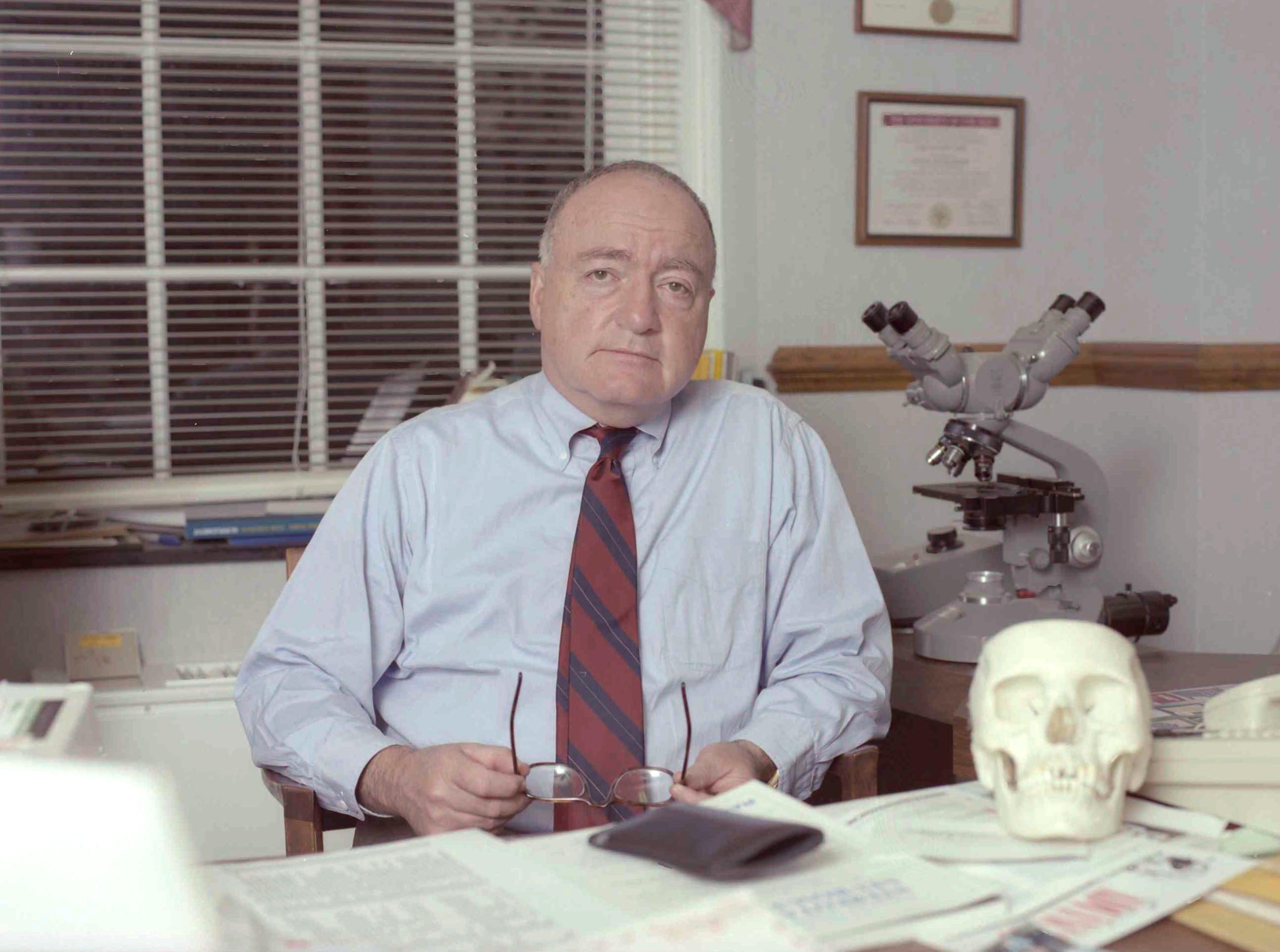 Dr. John Jane sits at his desk.