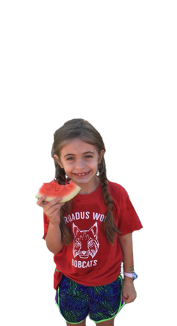 Anna, a small girl wearing a red shirt and eating a watermelon, stands and smiles.
