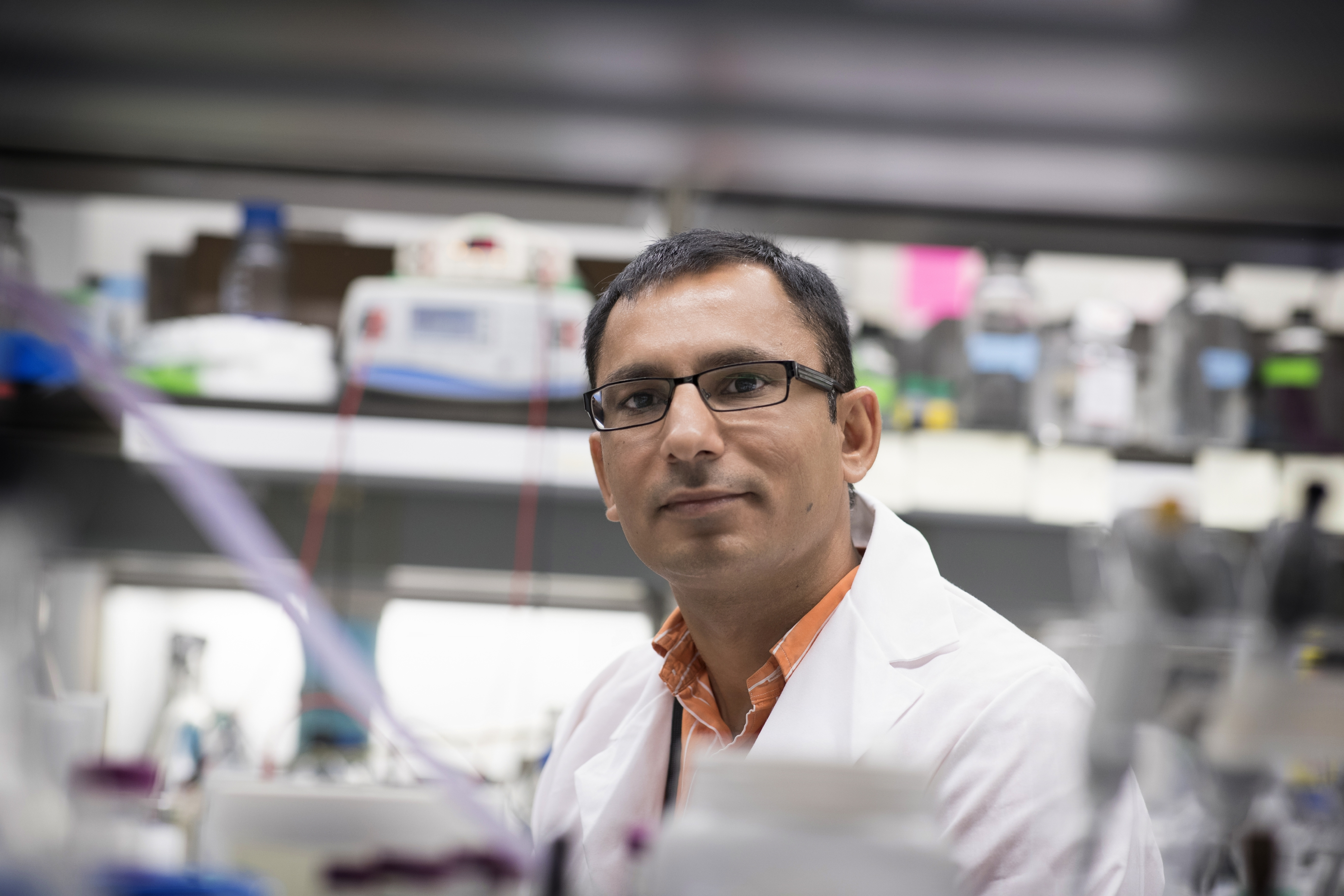 Jogender Tushir-Singh, PhD, stands in the lab