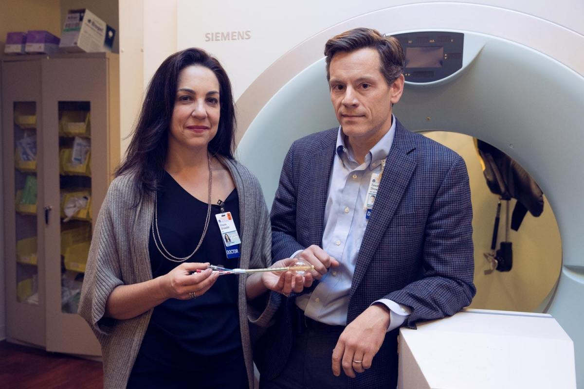 Dr. Shayna and Tim Showalter are shown standing in front of a radiation machine.