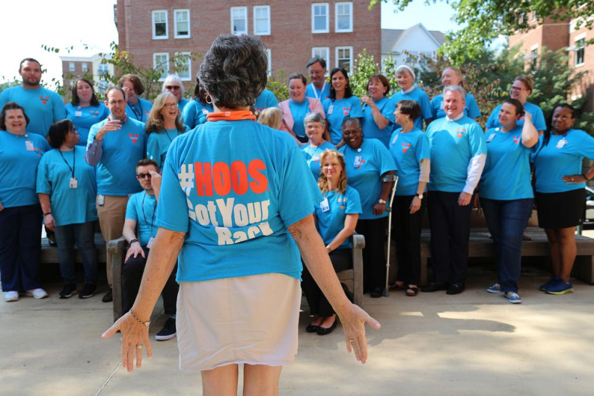 "Group of UVA employees stand together with ""#HOOS Got Your Back"" t-shirts."