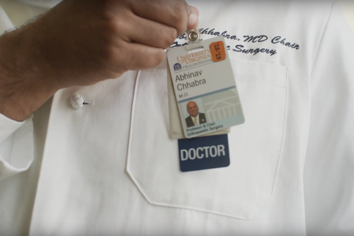 Dr. Chhabra's white coat, you see his hand hooking his medical badge to his pocket.
