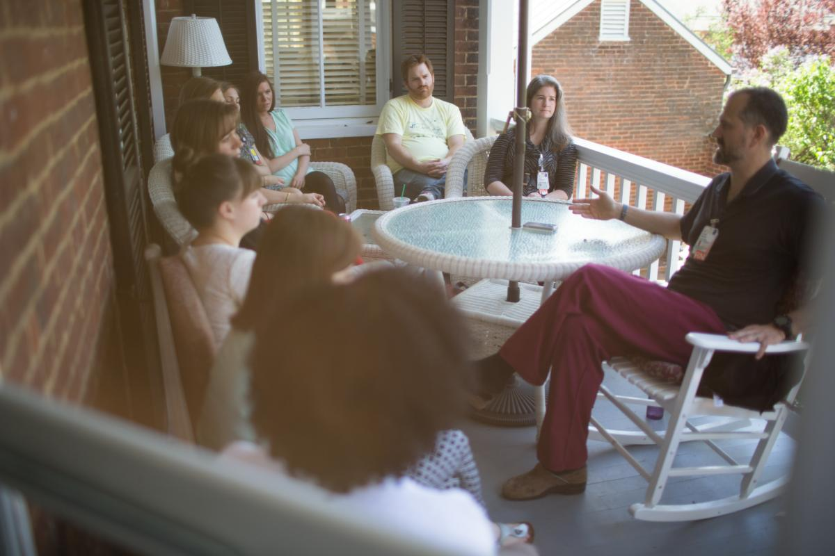 A School of Nursing class meets on the porch of a pavillion near the Rotunda.