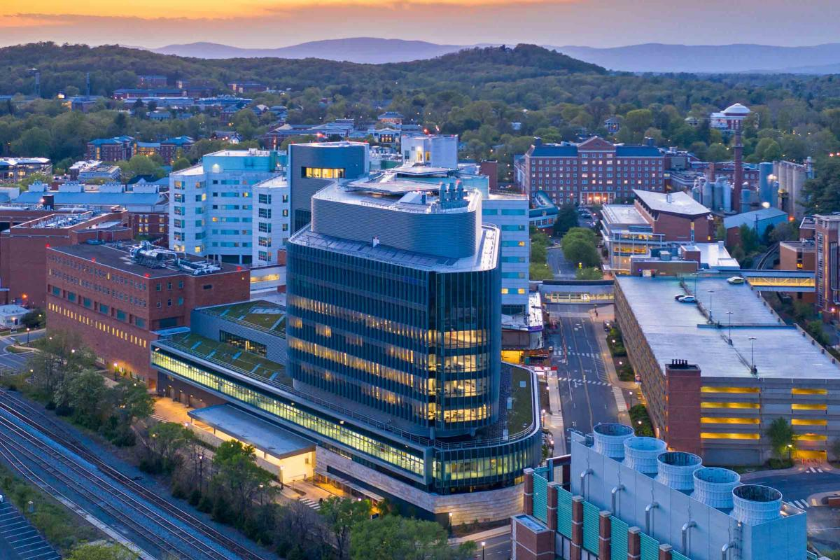 A photo of UVA hospital as the sun is rising over the mountains behind it.