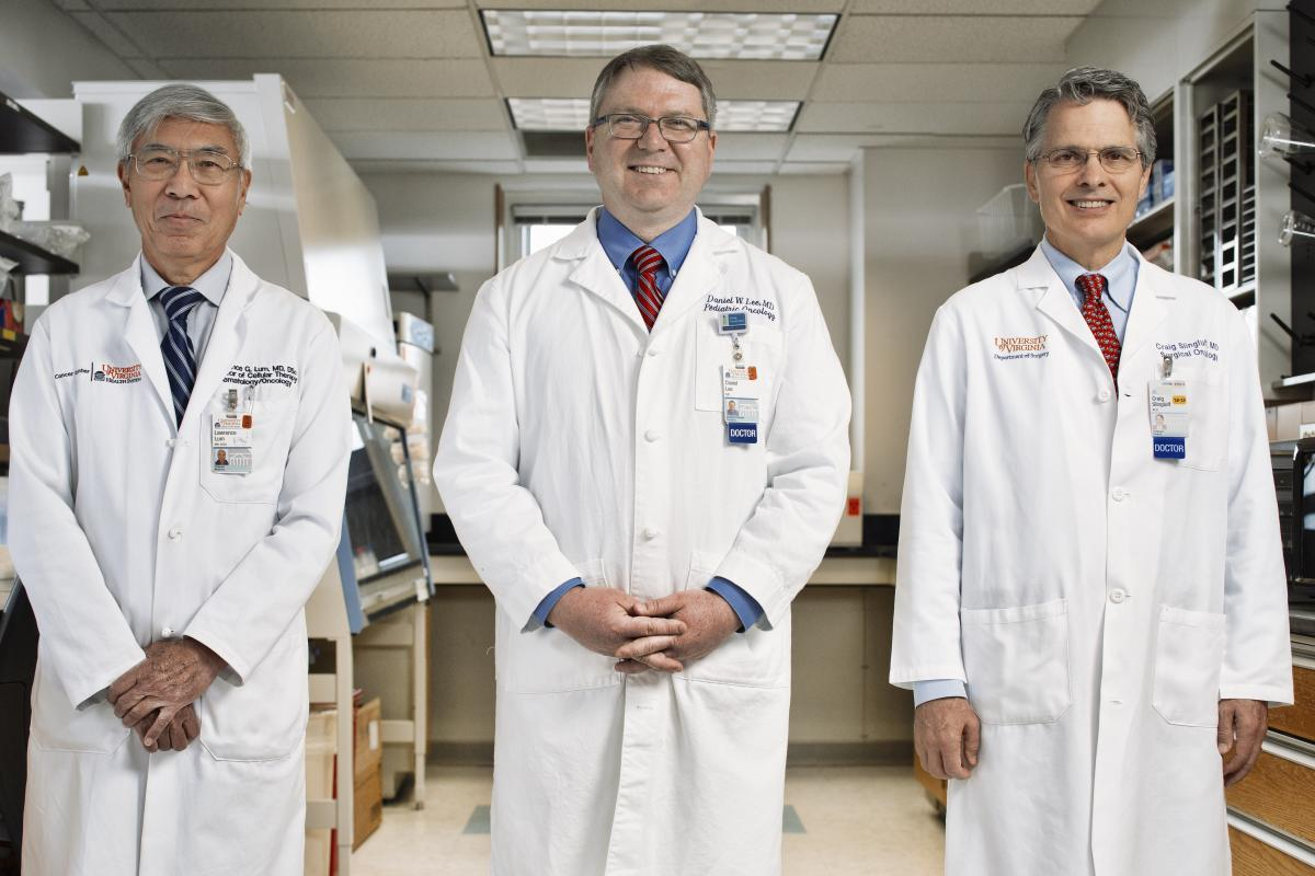 From left to right: Dr. Larry Lum, Dr. Trey Lee, and Dr. Craig Slingluff stand in their lab in their white coats
