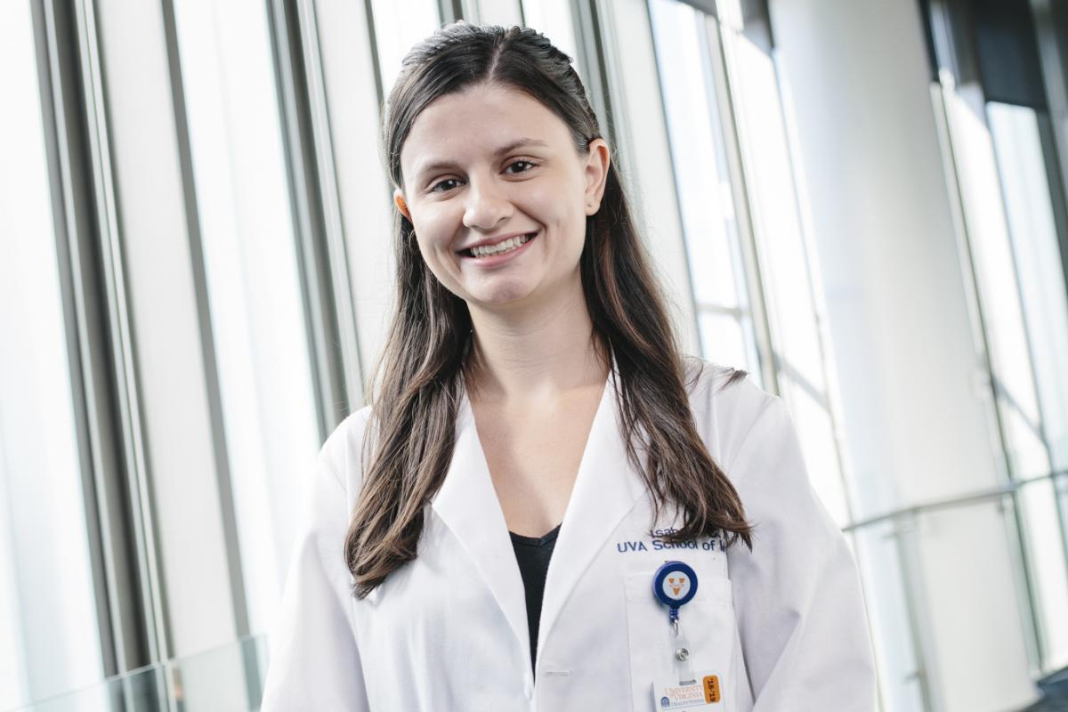 Isabelle Gill wears a white coat and stands in front of windows in a UVA Health building.