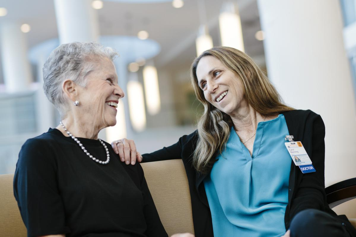 Patient Mary Ann Leeper and Dr. Carol Manning sit together in the hospital lobby and smile.