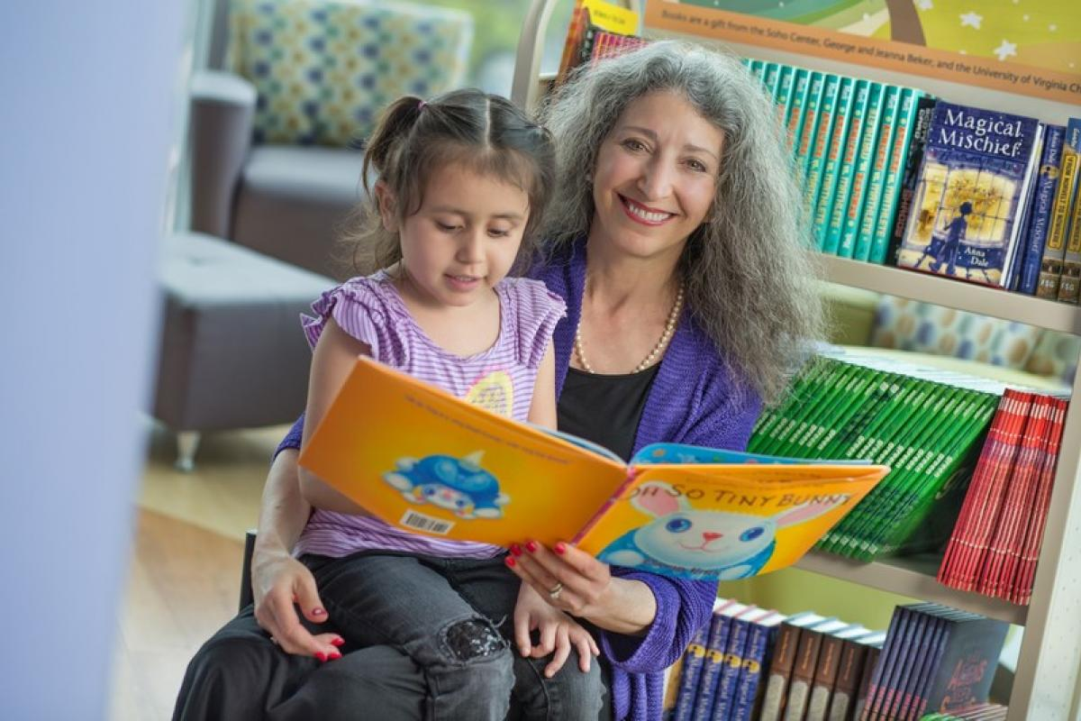 Soho Center Founder and Director Jeanna Beker shares a donated book with four-year-old Allison Valle.