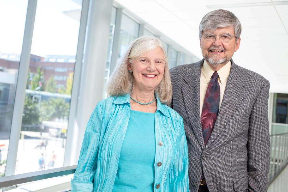 Martha and Dr. Geoffrey Weiss stand in a hallway overlooking UVA Health.