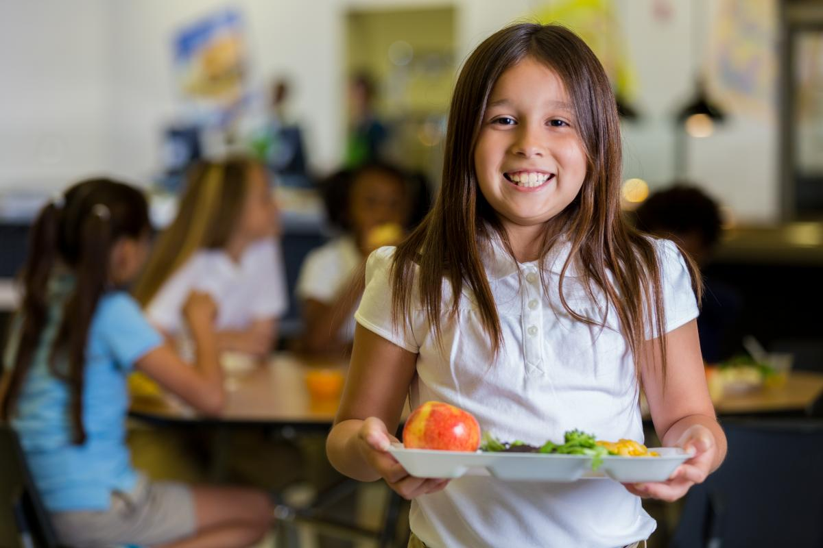 Girl stands with her lunch tray in a cafeteria.