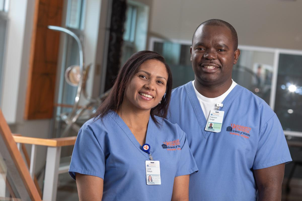 Paterson Ilunga and Lucie Ndaya stand in a classroom and smile in blue scrubs