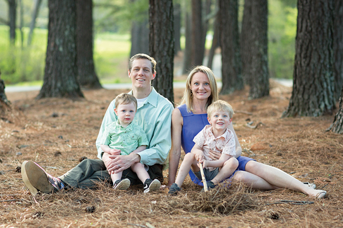 Dr. Kelleher sits on the ground in a forest next to her husband and her two sons.