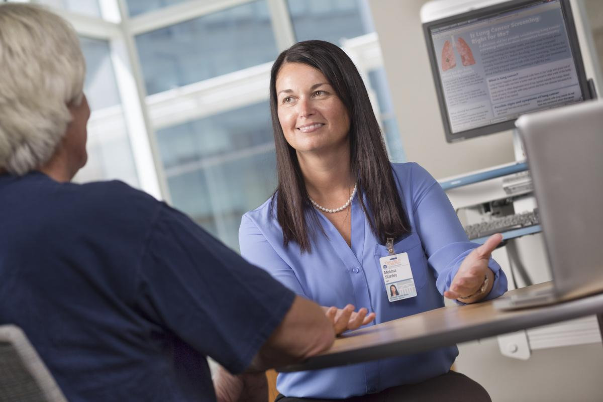 Nurse Melissa Stanley sits at a desk consulting with a patient