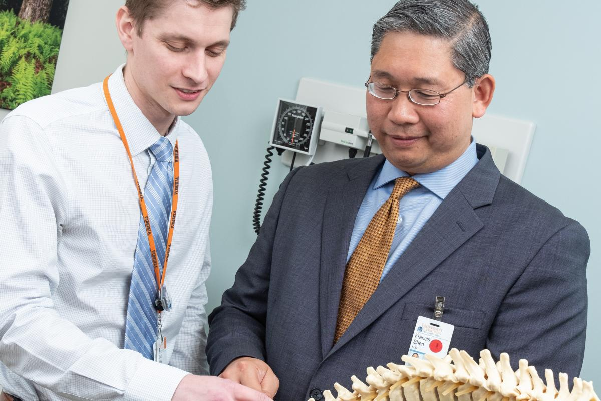 A resident stands beside Dr. Shen and they both examine vertebrae on a human skeleton spine.