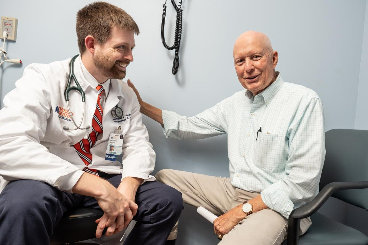 Bill Gregory, a cancer patient at UVA, sits smiling with his doctor Matthew Reilley.