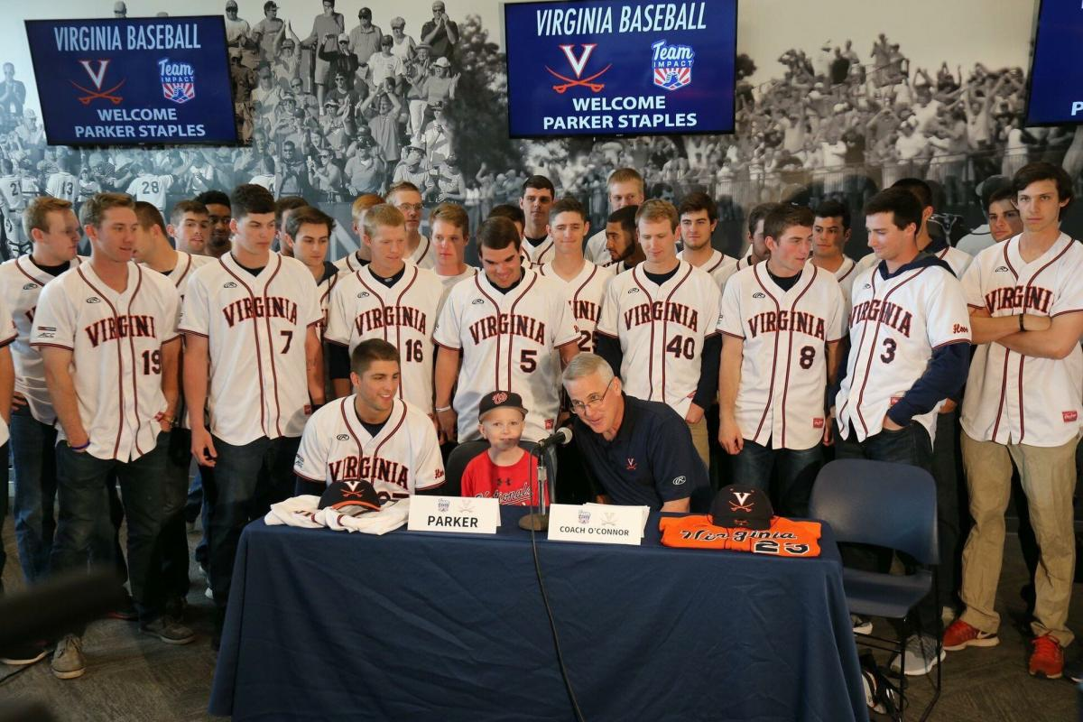 Nine-year-old Parker Staples sits with the UVA baseball team.