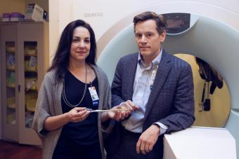 Drs. Shayna and Tim Showalter in front of an MRI machine.
